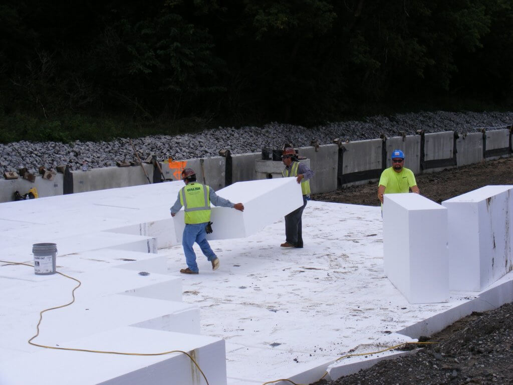 Construction workers installing Geofoam blocks for road construction